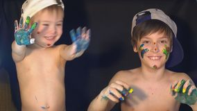 Two brothers draw color paints on the face. Family concept stock footage