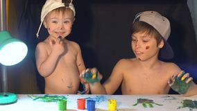 Two brothers draw color paints on the face. Family concept stock video footage