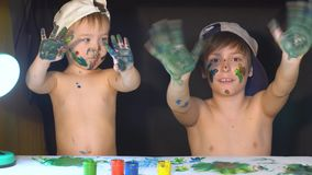 Two brothers draw color paints on the face. Family concept.  stock video footage