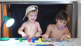 Two brothers draw fingers on paper. Their hands smeared with paint.  stock video footage