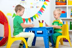 Two brothers draw pictures in the kids room. Royalty Free Stock Photo