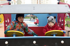 Two brothers driving toy car Royalty Free Stock Images