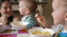 Two brothers eat porridge at home with their mother. They sit at one small table at home and eat with a spoon.  stock video footage