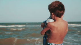 Two brothers. The elder brother holds his younger brother in his arms on the beach. A family. Brothers 2 years old and 9 years old stock video footage