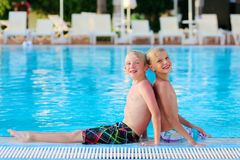 Two brothers enjoying swimming pool. Two happy boys, laughing teenage twin brother, enjoying sunny summer vacation playing with inflatable ball in outdoors Royalty Free Stock Images