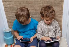 Two brothers, ages four and seven play games on smartphone and tablet. Two brothers of European appearance four and seven years old enjoys playing games on your Royalty Free Stock Photos