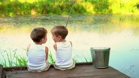 Two brothers fishing in the open air. Beautiful children have a good time in the summer on the lake. stock footage