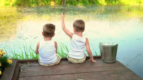 Two brothers fishing in the open air. Boys fish in white undershirts. stock video
