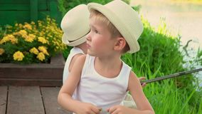 Two brothers fishing in the open air. Children in light hats sit on the bank of a pond with rods stock footage