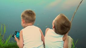 Two brothers fishing in the open air. Two little fishermen on fishing. Children in light hats sit on the bank of a pond. On this video you can see as two little stock video footage