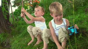 Two brothers fishing in the open air. Two little fishermen on fishing. Little brothers sit on the bank of a pond in the stock footage