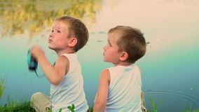 Two brothers fishing in the open air. Two small children catch fish in a pond at the dacha. The beautiful lake in summer stock video