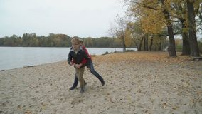 Two brothers have fun on the autumn beach. One of the boys holds and stops younger brother. Happy boys runs forward together. Adorable children have a good stock video footage
