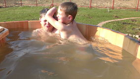 Two brothers having fun with splashes. In wooden barrel swimming pool stock footage