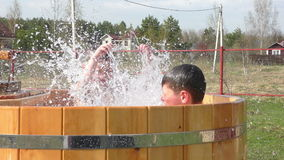 Two brothers having fun with splashes. In wooden barrel swimming pool stock video footage