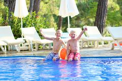 Two brothers having fun in swimming pool. Two happy boys, laughing teenage twin brother, enjoying sunny summer vacation playing with inflatable ball in outdoors Royalty Free Stock Photos