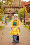 Two brothers hug in yellow jackets autumn.  stock photos