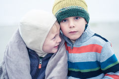 Two brothers hugging on the beach. Two young boys hugging on the beach royalty free stock photography