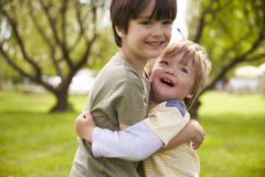 Two Brothers Hugging In Park Together royalty free stock images