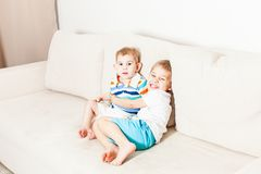 Two brothers hugging. On the white couch royalty free stock photos