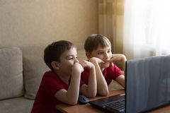Two brothers in identical red T-shirts watching cartoons in the computer at home. Family concept stock photos