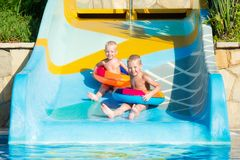 Two brothers in an inflatable rubber circles to hold hands and move down the water slide. royalty free stock photos