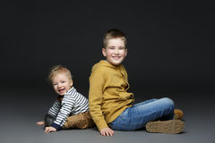 Two brothers in jeans sitting on floor. Two little boys in casual clothes sitting on floor over dark background. Brothers. Copy space Stock Photography