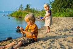 Two brothers kids play near lake with binoculars. Lake Uveldy, the Urals landscape, Russia Royalty Free Stock Photography