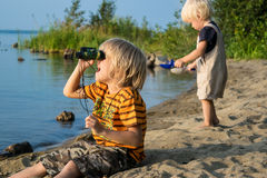 Two brothers kids play near lake with binoculars. Lake Uveldy, the Urals landscape, Russia Royalty Free Stock Image