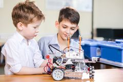 Two brothers kids playing with robot toy at school robotics class, indoor. Two little curious technicians of various ages playing with robotic car toy at at a royalty free stock images