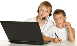 Two brothers with laptop. Doing homework  on white Royalty Free Stock Photo