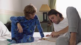 Two brothers lie down in bed, older brother read for small brother a book and high five stock footage