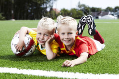 Two brothers lying on football field Stock Image