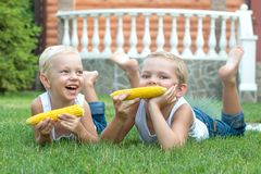 Two brothers lying on the grass and eat corn on the cob in the garden. .Two brothers stock photo