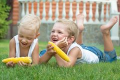 Free Two Brothers Lying On The Grass And Eat Corn On The Cob In The Garden Stock Photography - 141491532