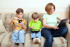 Two brothers and mother sit on divan. With electronic gadgets Royalty Free Stock Images