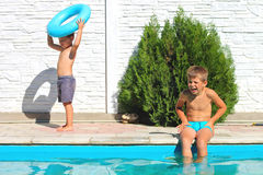 Two brothers near a swimming pool. At summer vacation Royalty Free Stock Image