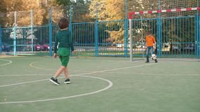 Two brothers play the ball. One kicks the ball on goal. The second goalkeeper stock footage