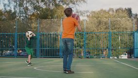 Two brothers play ball on the playground. Two brothers play the ball on the playground, throw the ball into the basketball hoop. One is dressed in shorts and a t stock footage
