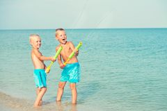 Two brothers play on the beach with water pistols. Summer time. royalty free stock photography