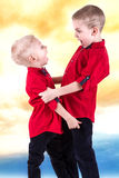 Two brothers play and have fun,spend time together.Children dressed in the same fashionable clothes,shirts. Children dressed in the same fashionable clothes stock images