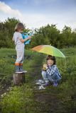 Two brothers play in rain outdoors stock images