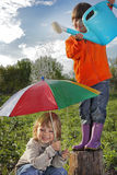Two brothers play in rain. Outdoors Stock Photos