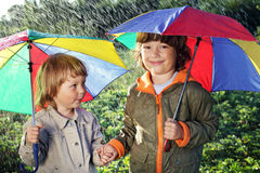 Two brothers play in rain. Outdoors Royalty Free Stock Photos