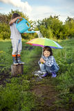 Two brothers play in rain. Outdoors Royalty Free Stock Images