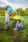 Two brothers play in rain. Outdoors Stock Photo