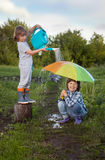 Two brothers play in rain outdoors.  Royalty Free Stock Image
