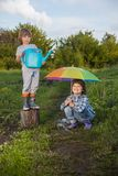 Two brothers play in rain outdoors.  Royalty Free Stock Photo