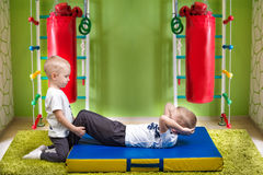 Two brothers play sports.Doing abdominal exercises .Sport and health. Doing abdominal exercises .Sport and health royalty free stock photo