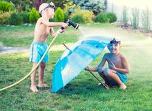 Two brothers play on a summer hot day in the garden. Children are splashing with a garden hose. Children are splashing with a garden hose.Two brothers play on royalty free stock photography